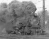 A close up black and white photo of a L1s 2-8-2 Mikado steam locomotive coming down the tracks with big black smoke coming out of its chimney