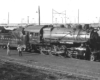 A black and white photo of a H9 2-8-0 Consolidation No. 3529 locomotive in a rail yard with two people talking next to it