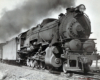 A black and white close up photo of a 2-10-0 steam locomotive with some smoke coming out of its chimney