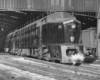 A black and white photo of a locomotive leaving a station