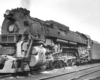 A close up black and white photo of a trains on the tracks