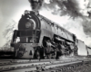 A close up black and white photo of a Q2 6187 locomotive coming own the tracks with big smoke coming out of its chimney