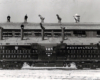 A black and white full length picture of a Lima-Hamilton 2,500 h.p. twin-engine transfer unit No. 8948 locomotive in front of a building