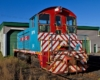 A red and white train parked outside an enginehouse