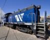 A blue train sitting outside a shop