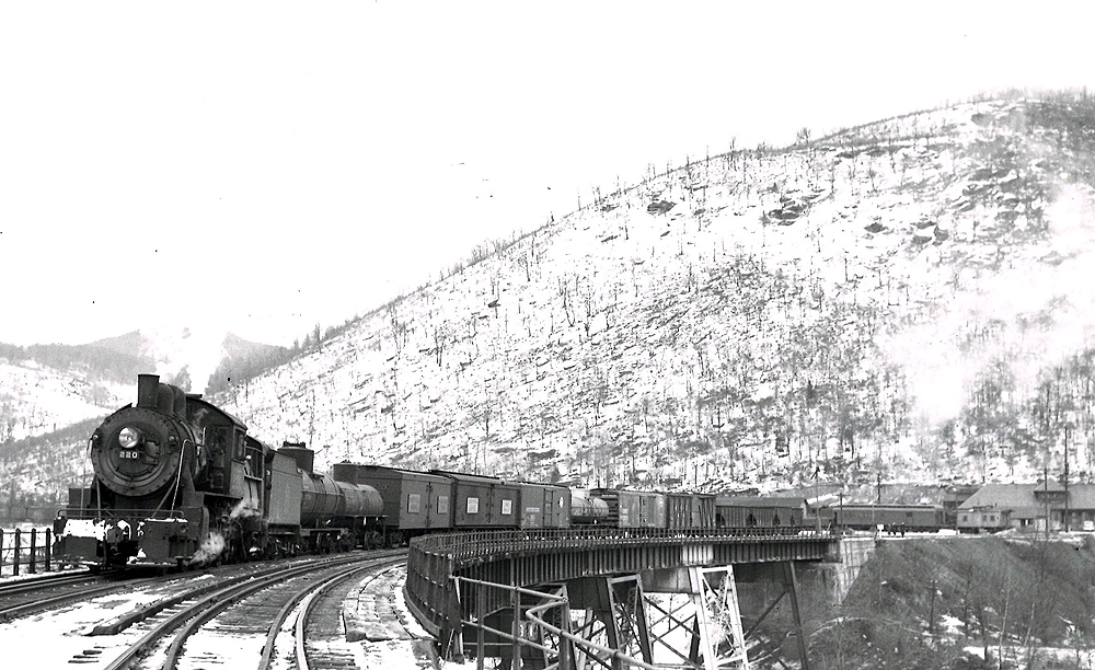 Steam locomotive with freight train on curved trestle