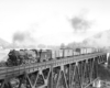 Steam locomotive with freight train on deck-truss bridge