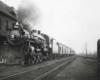 a steam engine pulling passenger cars