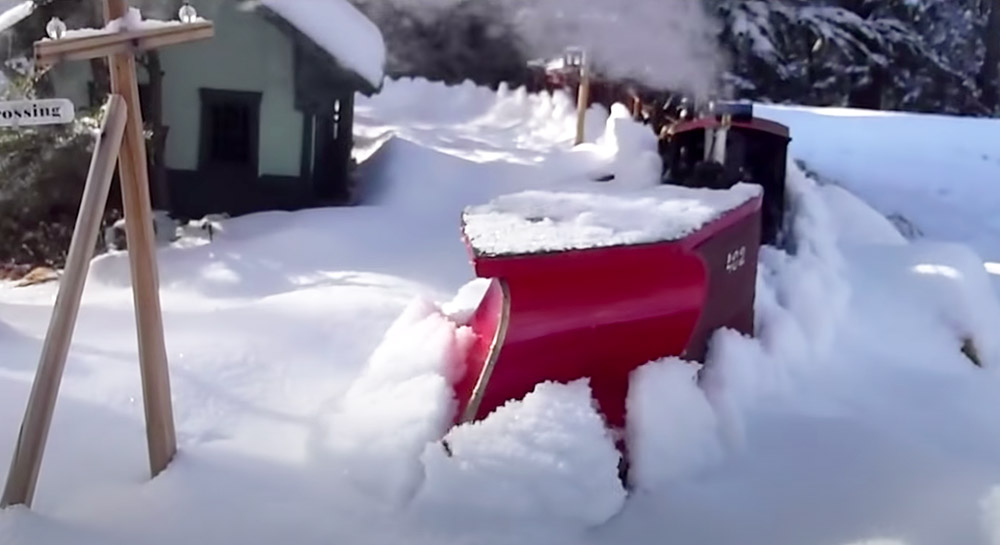 plow being pushed by model train to clear snow on a garden railroad