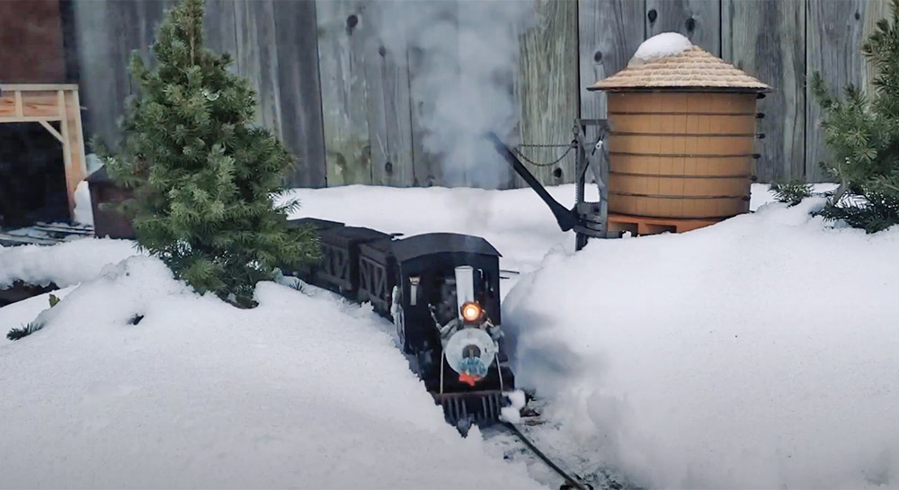 model train running on a snowy garden railway