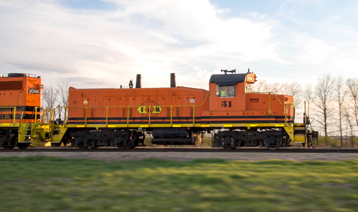 Older orange locomotive leading a train in late afternoon sunlight.