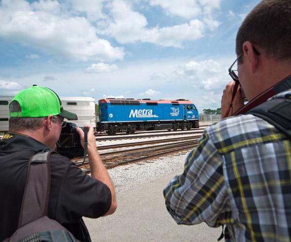 Two men filming blue train