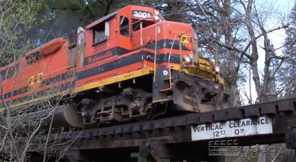 Close-up image of an orange-painted diesel locomotive on a trestle.