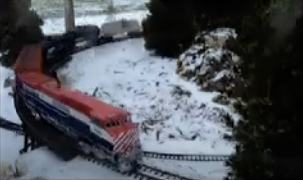 trains running in winter on a garden railroad