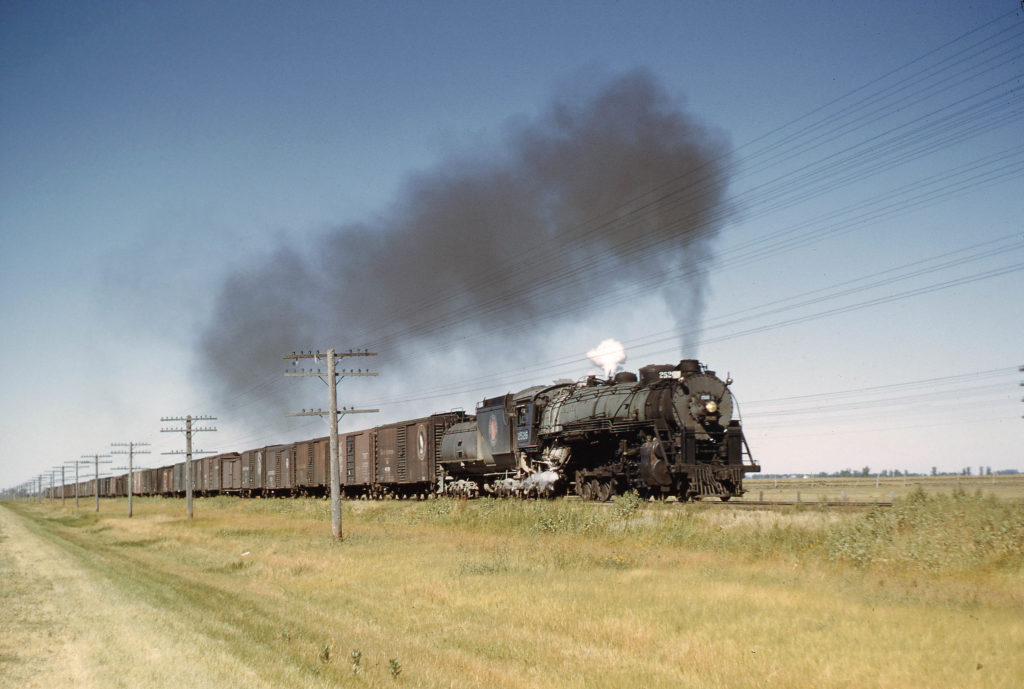 Steam locomotive with boxcars on prairie