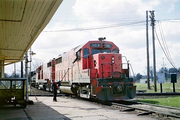 An engineer receives paper orders from a hoop in a red-painted locomotive leading a freight train.