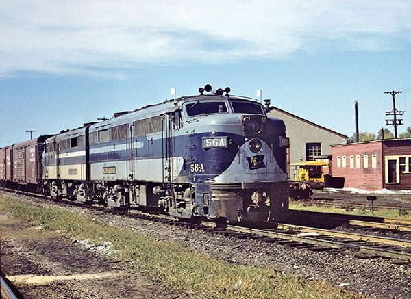 Two blue diesel cab locomotives lead a freight train.