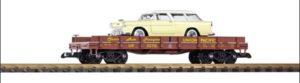 Flatcar carrying a yellow station wagon