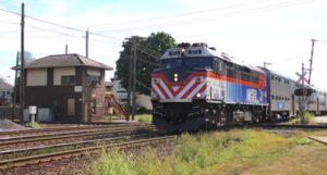 Passenger train passes brick interlocking tower