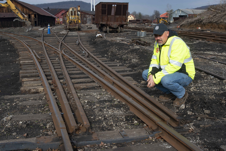 Man in high-visibility clothing squats near rust covered rails of a switch in a rail yard.