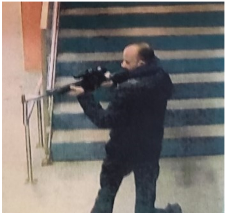 Grainy image of balding man holding and appearing to aim a long gun in front of steps.