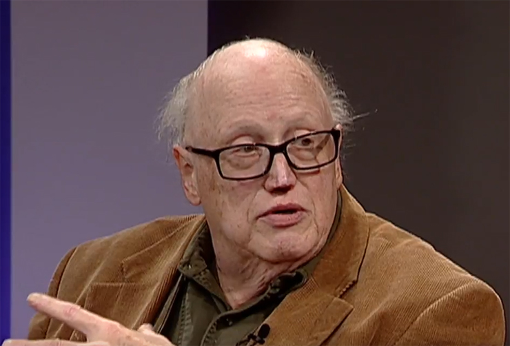 Balding caucasian man wearing eyeglasses and brown coat.