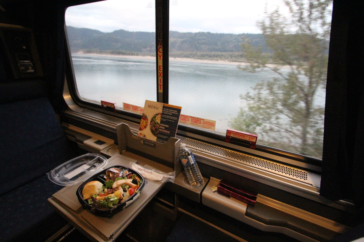 A meal on a small table in a passenger car overlooking a river.