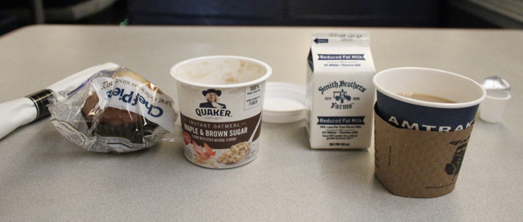 From left: packaged muffin, oatmeal in a paper cup, small milk carton, what appears to be coffee in a paper cup.