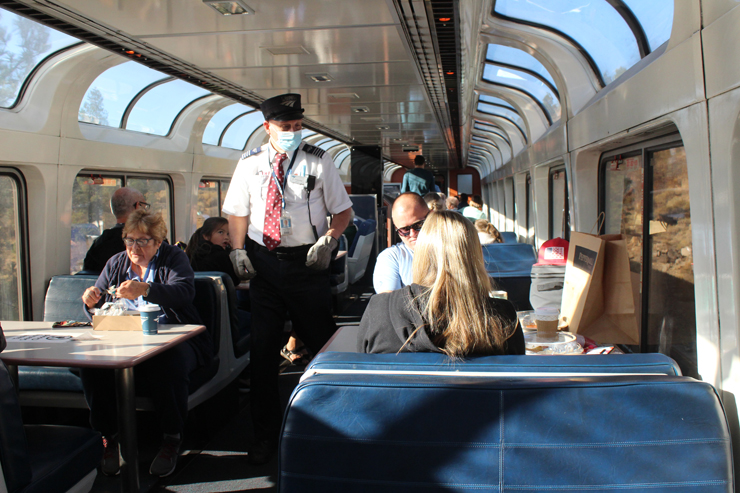 Masked Amtrak employee walking center aisle of a passenger car with broad arching windows.
