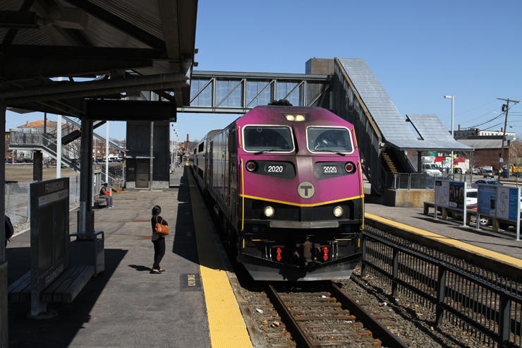 A purple painted locomotive heads a train surrounded by a passenger platform on a cloudless day.