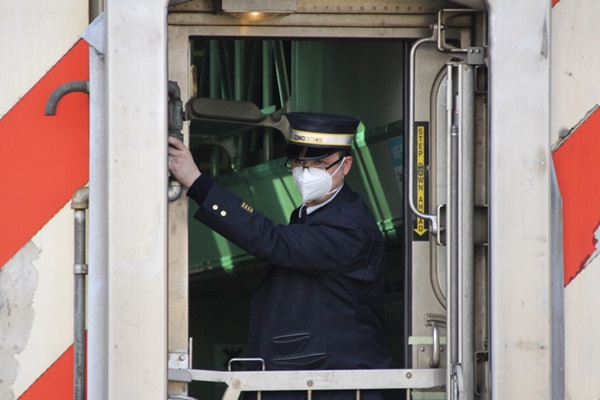 A train conductor wearing a mask