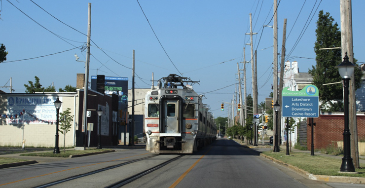 A silver painted passenger train operates in the middle of a street.
