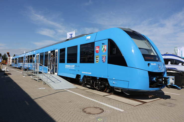 A blue-painted passenger train under mostly clear skies.