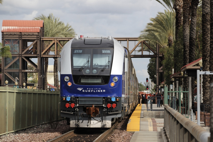 Blue and silver-painted locomotive at a station platform surrounding by brown steel work and palm trees.