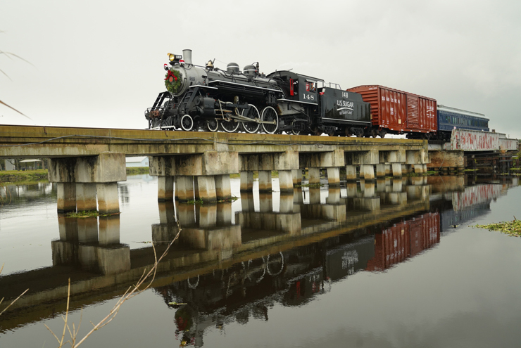 Steam locomotive pulling train over water on a pile causeway.