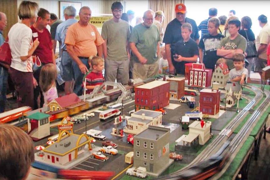 A group of people standing around an O gauge layout