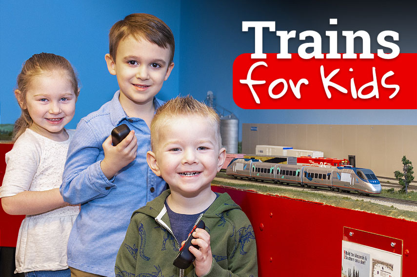 Two young boys and a girl holding controllers in front of a HO layout