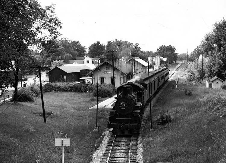 Ann Arbor 4-4-2 steam locomotive with passenger train at station.