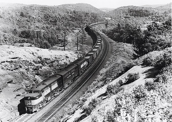 Three streamlined diesel locomotives with freight train in mountains.