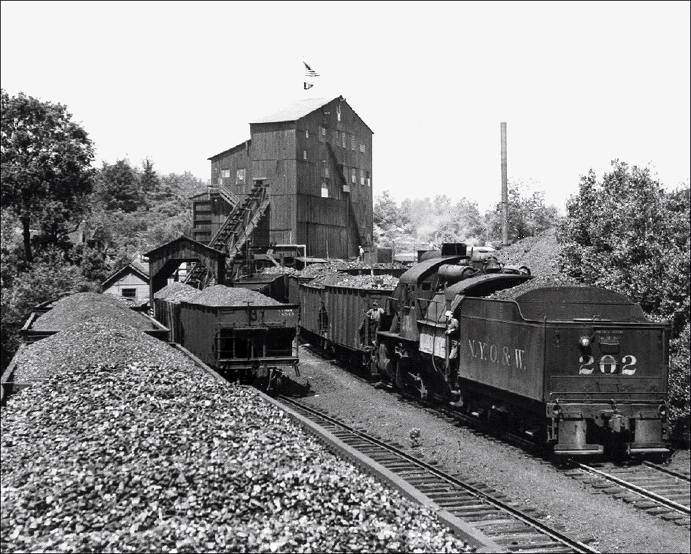 Coal hoppers being switched by a camelback steam locomotive and loaded with coal.