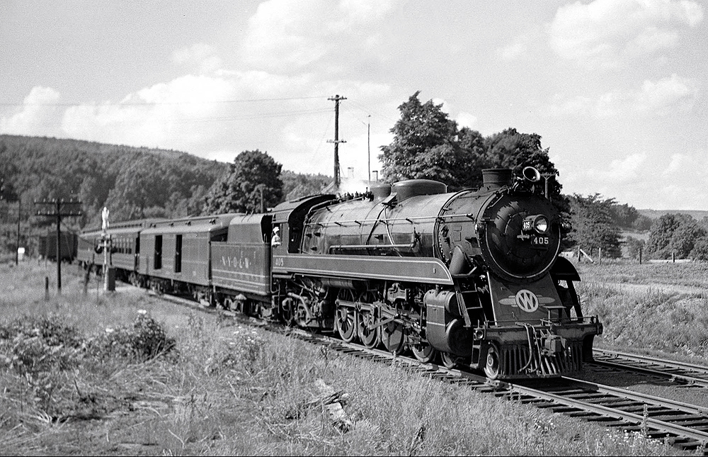 A steam locomotive hauls a passenger train through a forest-and-field covered valley.
