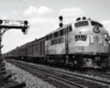 One cab unit diesel locomotive leads a passenger train over a multi-track mainline.