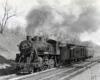 A steam locomotive leads a two-car passenger train through a cut.