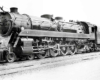 Angled front image of a 4-8-2 steam locomotive.