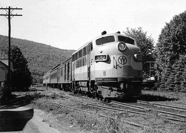 Cab unit diesel locomotive leads a passenger train.