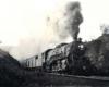 A steam locomotive leads a passenger train through a rock cut.