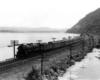 A steam locomotive leads a long train on a causeway between two water bodies at the foot of a mountain.