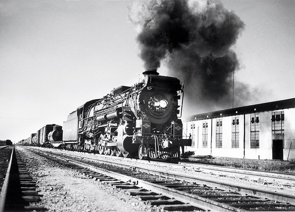 Steam locomotive hauling freight train emitting large plume of smoke.
