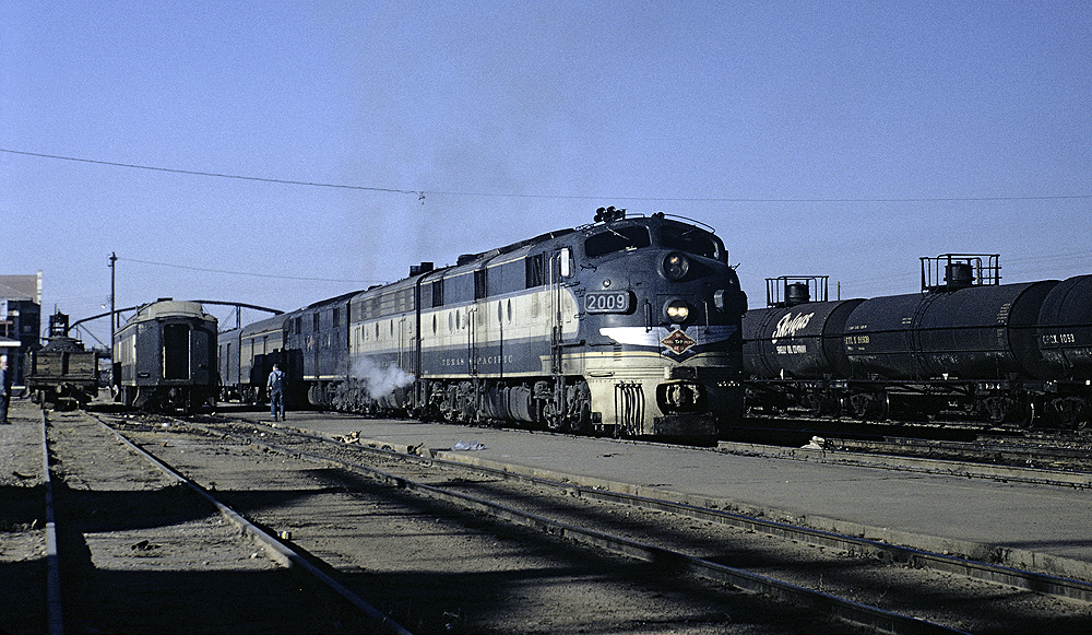 Blue and yellow painted diesel locomotives hauling a train.