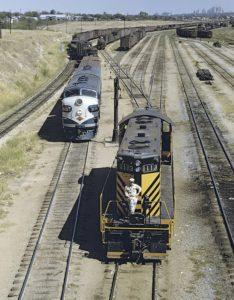 Two diesel locomotives appear in a rail yard.